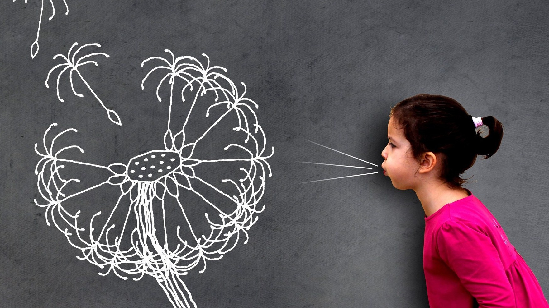Photo: Jack Moreh - Little cute girl blowing dandelion seeds on chalkboard
